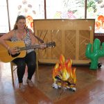 A woman playing the guitar in front of a piano and cardboard cutout of a fire.