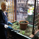 A woman resident gardening in a window box.