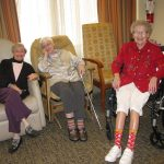 3 elderly women residents smiling and lounging.