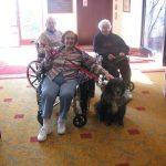 A resident in a wheelchair with her black dog and other residents nearby.