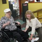 A wheelchair-bound resident receiving assistance from a woman.